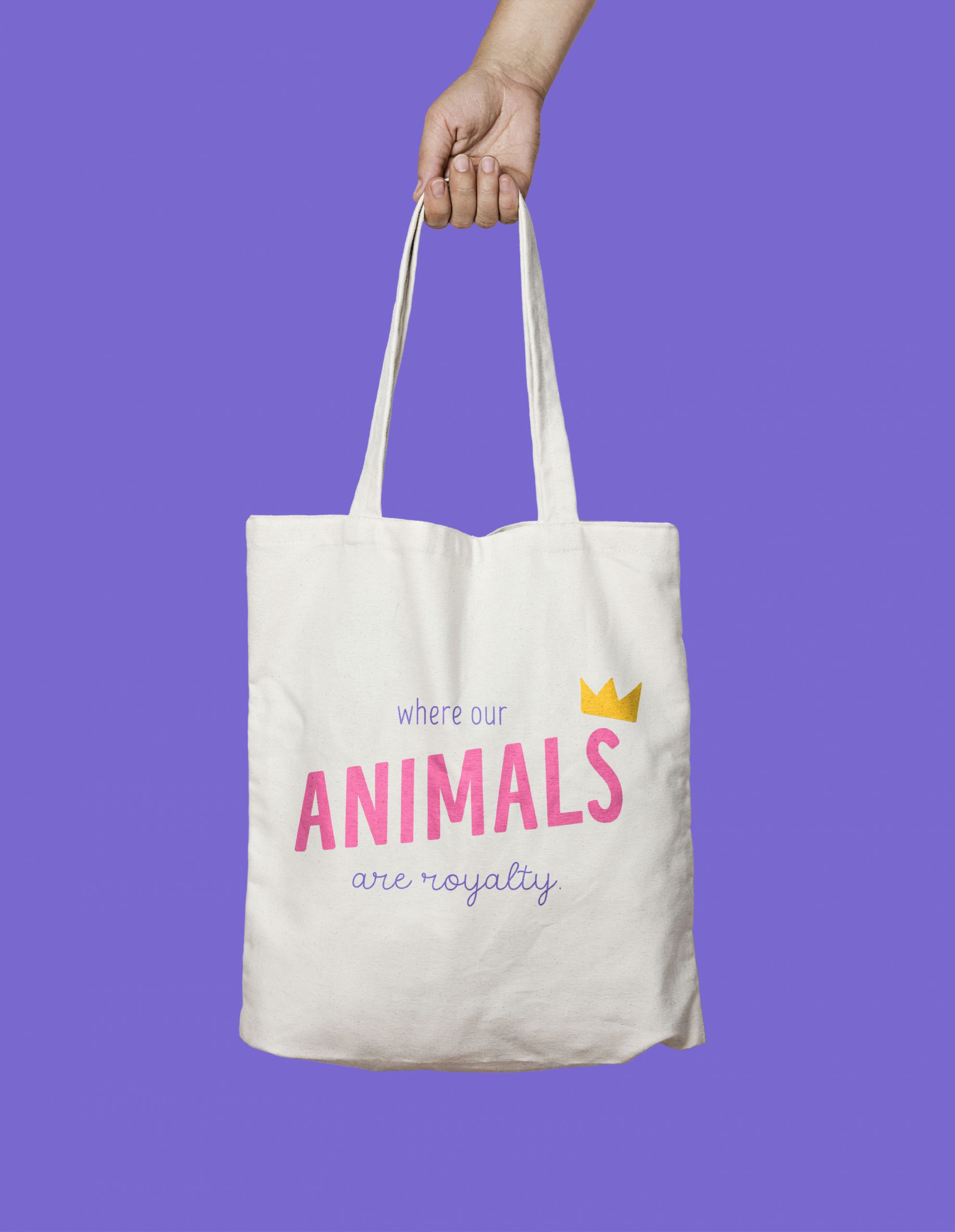 Hand holding a Where our animals are royalty canvas bag