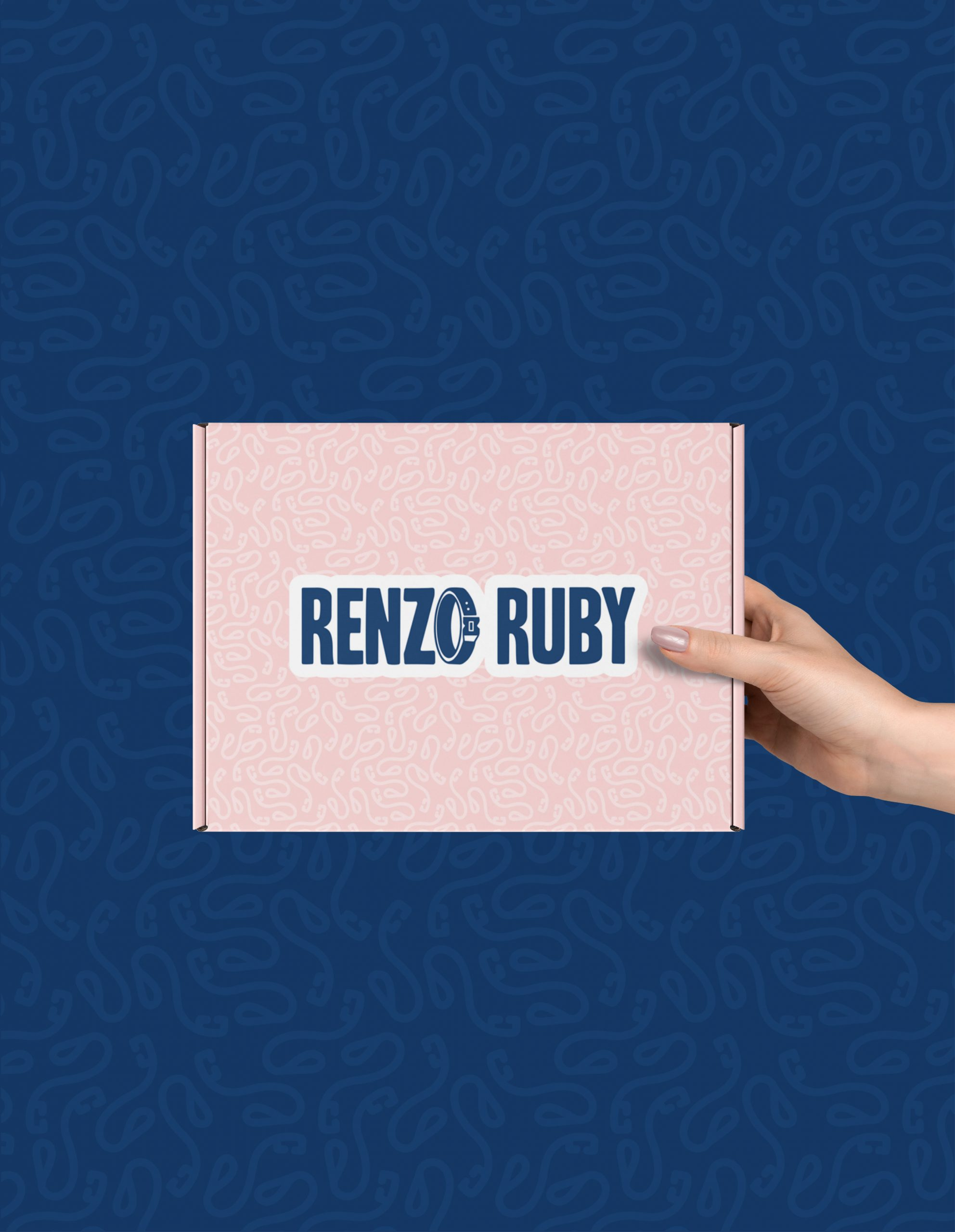 hand holding pink box with blue Renzo and Ruby logo