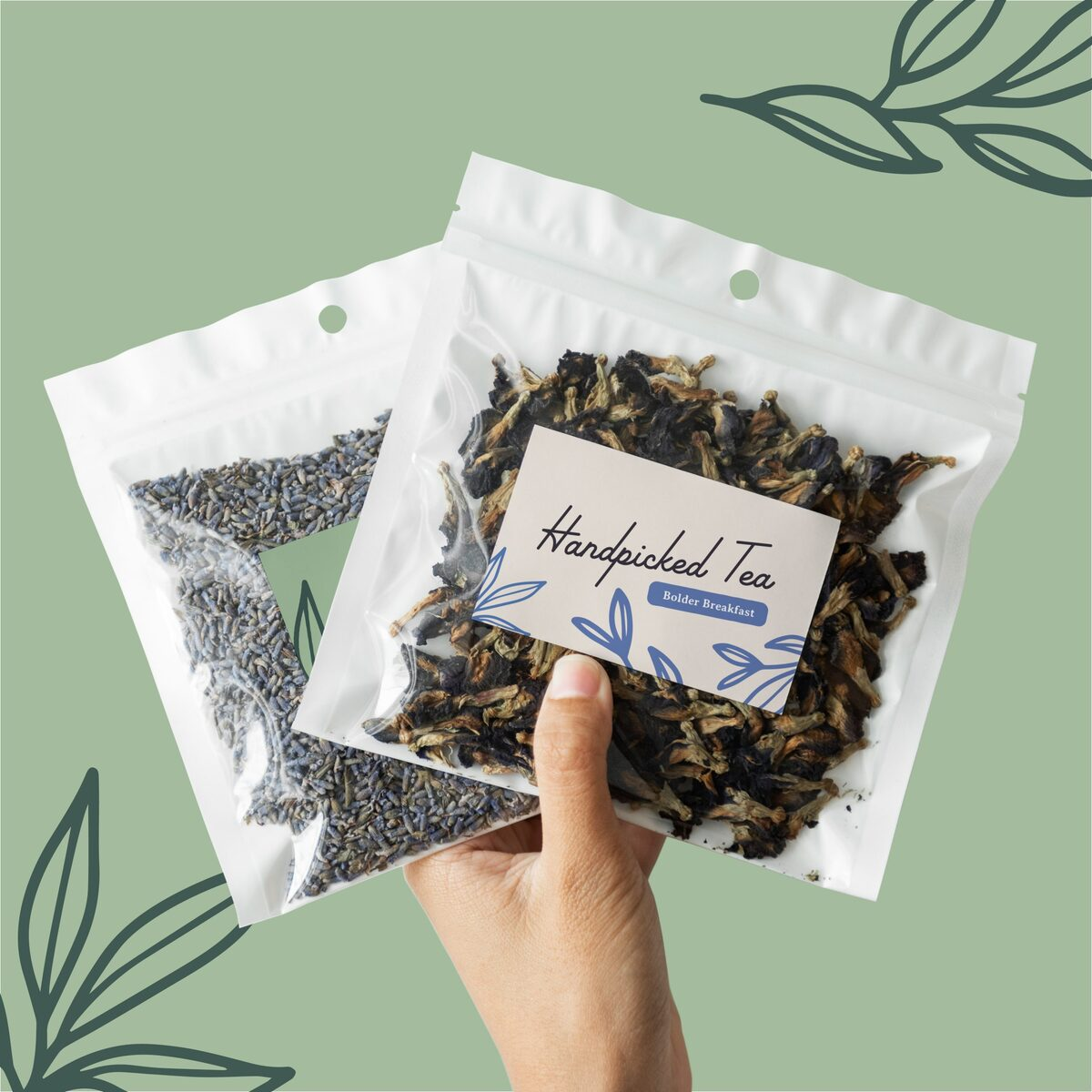 Hand holding up two bags of handpicked tea